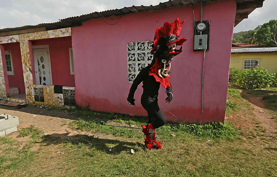 "A man dressed in a devil costume walks home to take a break from the Devils and Congos carnival ritual, in Nombre de Dios, Panama, Wednesday, Feb. 18, 2015. The Ash Wednesday ritual involves ""devils"" dancing through the streets in the guise of looking for and scaring ""sinners"" among the merry residents who have been partying for four days. On the final day of their festivities the residents work to avoid being caught by a devil. The celebration dates to colonial times in which devils represented the Spanish conquerors and the 'Congos' represented escaped African slaves. (AP Photo/Arnulfo Franco)"