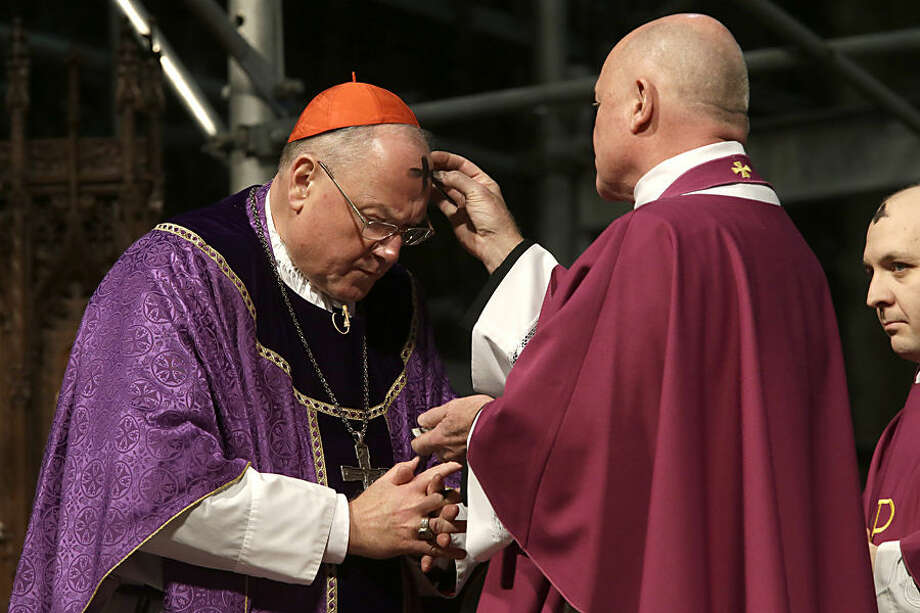 Monsignor Robert Ritchie, right, places ashes on Cardinal Timothy Dolan's forehead during an Ash Wednesday Mass at St. Patrick's Cathedral, Wednesday, Feb. 18, 2015 in New York. Ash Wednesday marks the start of the Lent, a season of prayer and fasting for Christians before Easter. (AP Photo/Mary Altaffer)