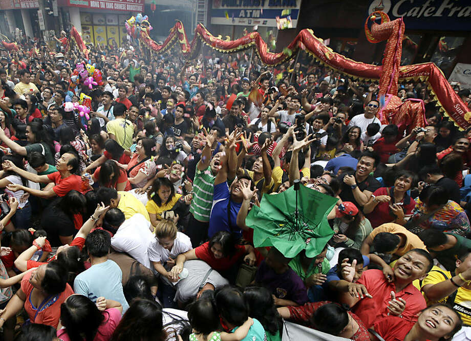 """Crowd catch sweets and giveaways being thrown at them following dragon and lion dances performed in front of a supermarket at Manila's Chinatown district of Binondo to celebrate the Chinese New Year Thursday, Feb. 19, 2015, Philippines. This year marks the """"Year of the Sheep"""" in the Chinese Lunar calendar. (AP Photo/Bullit Marquez)"""