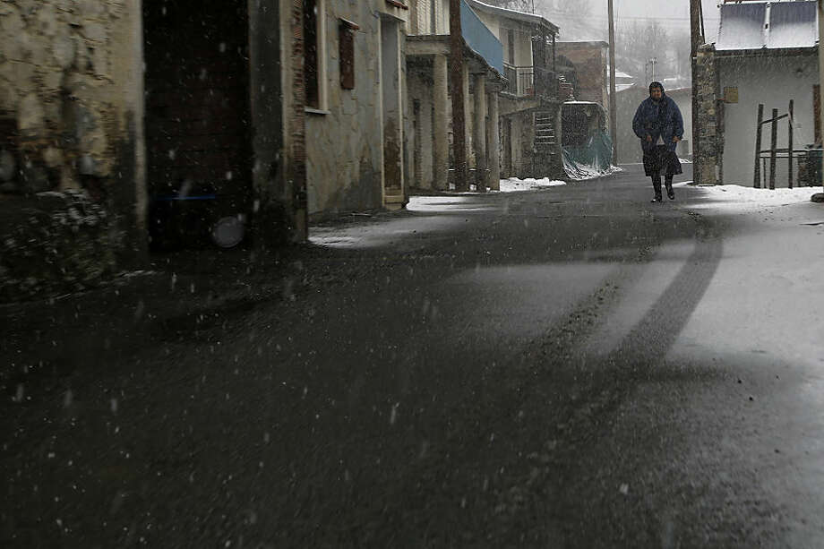 An elderly woman walks during a snowfall in Kiperounta village on Troodos mountains, Cyprus, Thursday, Feb. 19, 2015. The cold front brought unseasonably cold temperatures and plenty of snow on Cyprus' Troodos mountain range. Schools were closed in many small mountain villages and communities as a result of the snowfall that made roads treacherous. Even the capital Nicosia saw rare snow flurries. Temperatures are forecast to rise over the weekend. (AP Photo/Petros Karadjias)