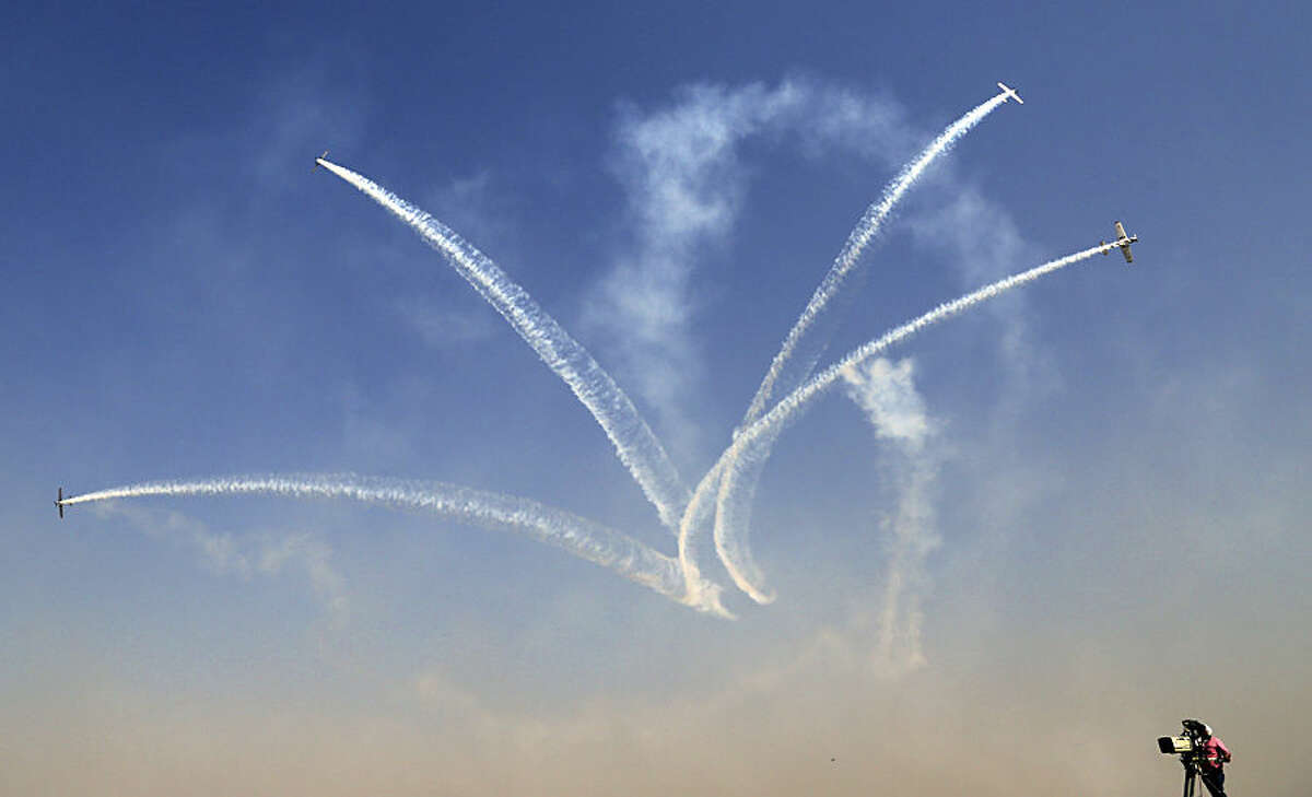 A cameraman films as Russian aerobatic team Yakovlev performs at the inaugural function of Aero India 2015 at Yelahanka air base in Bangalore, India, Wednesday, Feb. 18, 2015. Aviation companies from around the world are participating in the five-day event which runs through Feb. 22. (AP Photo/Aijaz Rahi)