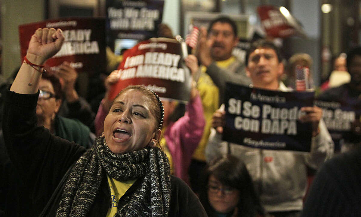 Mercedes Herrera and others chant during an event on DACA and DAPA Immigration Relief at the Houston International Trade Center, Tuesday, Feb. 17, 2015, in Houston. The White House promised an appeal Tuesday after a federal judge in Texas temporarily blocked President Barack Obama's executive action on immigration and gave a coalition of 26 states time to pursue a lawsuit aiming to permanently stop the orders. (AP Photo/Houston Chronicle, Melissa Phillip)
