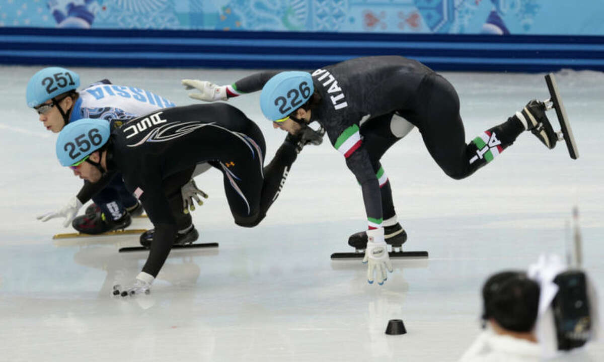 Eduardo Alvarez of the United States, left, loses his balance with Yuri Confortola of Italy, right, in a men's 1500m short track speedskating semifinal at the Iceberg Skating Palace during the 2014 Winter Olympics, Monday, Feb. 10, 2014, in Sochi, Russia. (AP Photo/Ivan Sekretarev)