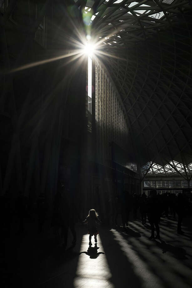 A girl walks in a shaft of light on the main concourse at King's Cross railway station, London, Wednesday, Feb. 18, 2015. More than 29 million passengers annually rely on mainline train services from King's Cross, according to the British Office of Rail Regulation, making it the ninth busiest station in the country. (AP Photo/David Azia)