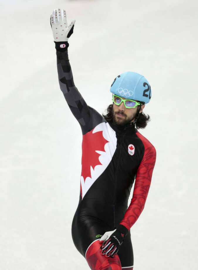Charles Hamelin of Canada waves to spectators after competing in a men's 1500m short track speedskating semifinal at the Iceberg Skating Palace during the 2014 Winter Olympics, Monday, Feb. 10, 2014, in Sochi, Russia. (AP Photo/Ivan Sekretarev)