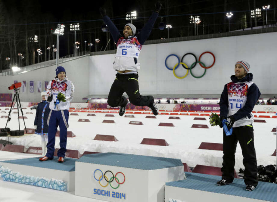 Gold medal's winner France's Martin Fourcade, center, jumps in celebration flanked by with silver medalist Czech Republic's Ondrej Moravec, left, and bronze medalist France's Jean Guillaume Beatrix, during the flowers ceremony for the men's biathlon 12.5k pursuit, at the 2014 Winter Olympics, Monday, Feb. 10, 2014, in Krasnaya Polyana, Russia. (AP Photo/Kirsty Wigglesworth)