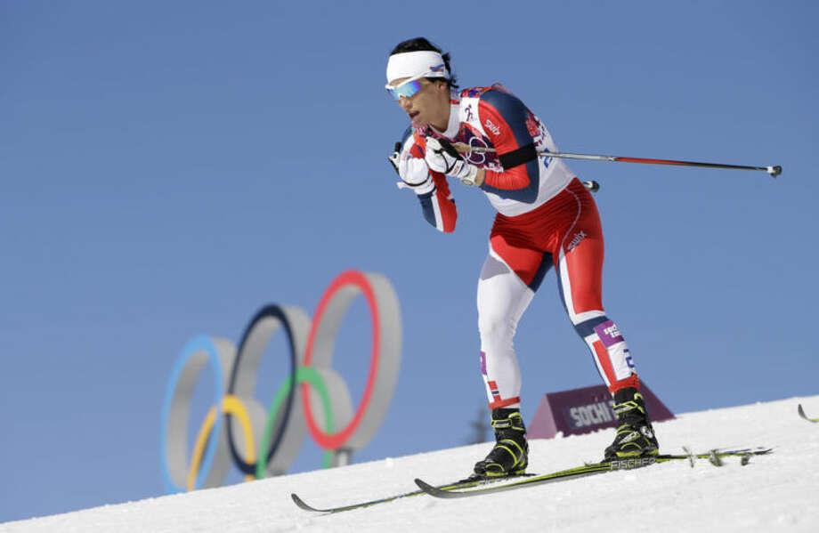 Norway's gold medal winner Marit Bjoergen skis past the Olympic rings during the women's cross-country 15k skiathlon at the 2014 Winter Olympics, Saturday, Feb. 8, 2014, in Krasnaya Polyana, Russia. (AP Photo/Lee Jin-man)