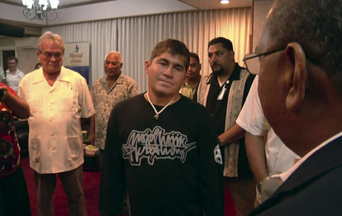 In this video image taken from AP video, Jose Salvador Alvarenga, center, a Salvadoran man who says he drifted in an open boat across the Pacific for more than a year, bids farewell to Marshall Islands President Christopher Loeak, right, before flying home at an airport in Majuro, Marshall Islands Monday, Feb. 10, 2014. Alvarenga thanked people for taking care of him after he washed ashore in the island nation late last month and said he was
