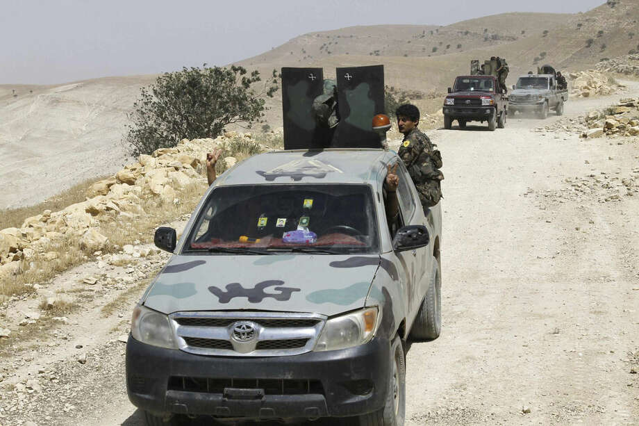 FILE - In this file photo released on May 20, 2015, provided by the Kurdish fighters of the People's Protection Units (YPG), which has been authenticated based on its contents and other AP reporting, Kurdish fighters of the YPG stand on their vehicles on their way to battle against the Islamic State, near Kezwan mountain, northeast Syria. A spokesman for a powerful Syrian Kurdish political party said on Wednesday, March 16, 2016 that his faction is planning to declare a federal region in northern Syria, a model it hopes can be applied to the entire country. (The Kurdish fighters of the People's Protection Units via AP, File)