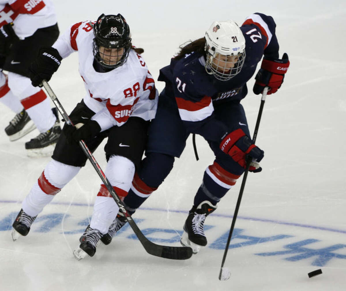 Hilary Knight of the Untied States takes the puck away from Phoebe Stanz of Switzerland during the second period of the 2014 Winter Olympics women's ice hockey game at Shayba Arena, Monday, Feb. 10, 2014, in Sochi, Russia. (AP Photo/Petr David Josek)