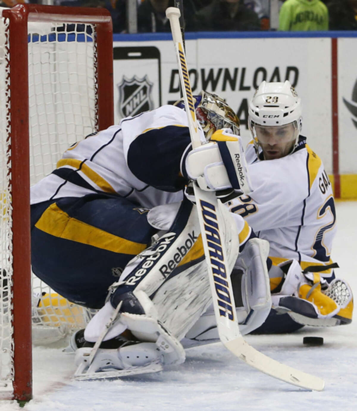 Nashville Predators center Paul Gaustad (28) watches as Predators goalie Pekka Rinne (35) of Finland, makes a save in the second period of an NHL hockey game at Nassau Coliseum in Uniondale, N.Y., Thursday, Feb. 19, 2015. (AP Photo/Kathy Willens)