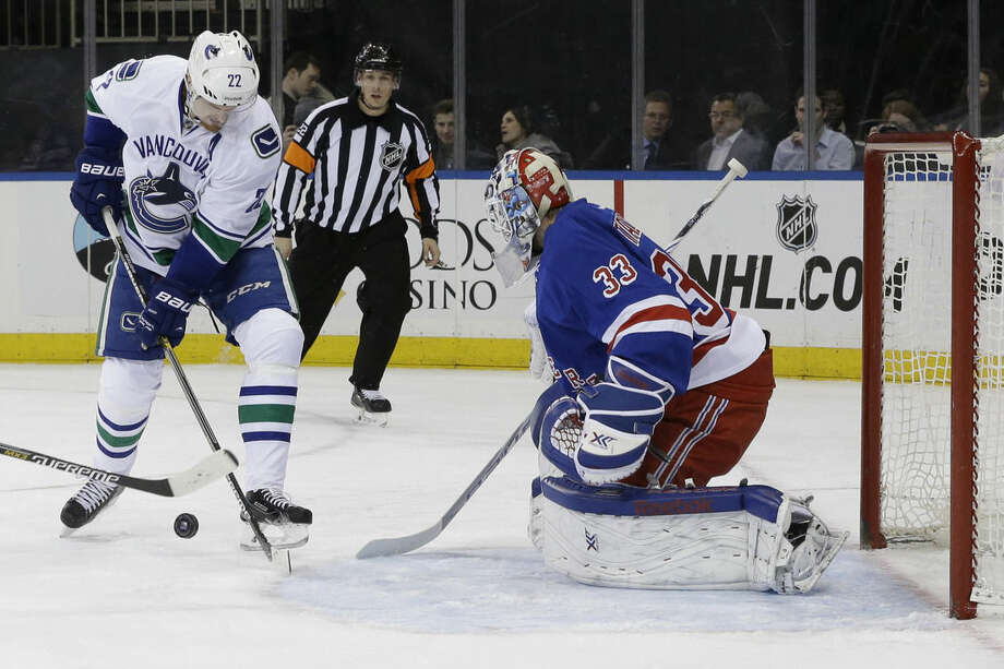 New York Rangers goalie Cam Talbot defends the net against Vancouver Canucks left wing Daniel Sedin during the first period of the NHL hockey game, Thursday, Feb. 19, 2015, at Madison Square Garden in New York (AP Photo/Mary Altaffer)