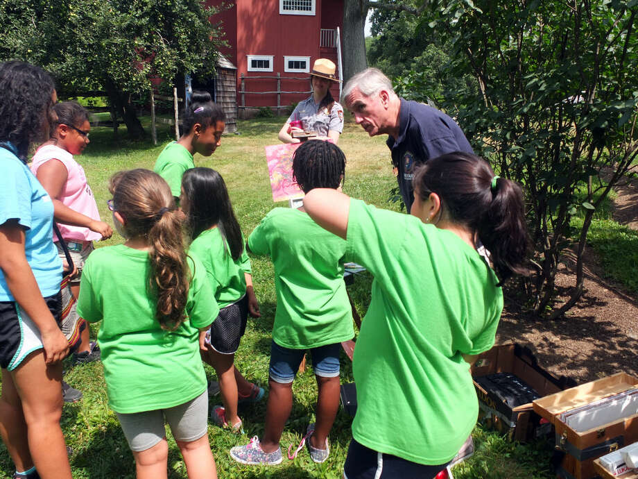 A Weir Farm volunteer guides a group of Girl Scouts around the historical site.