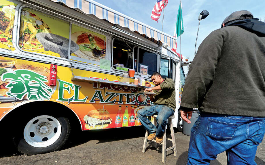Hour photo / Erik Trautmann Customers including Sal Argueta, left, order food from Tacos El Azteca on Main St. in Norwalk Wednesday. The Norwalk Common Council may revisit the fee food vendors must pay annually.