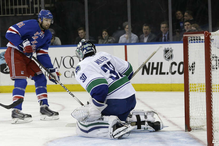 New York Rangers left wing Rick Nash (61) scores a goal past Vancouver Canucks goalie Ryan Miller during the second period of an NHL hockey game, Thursday, Feb. 19, 2015, at Madison Square Garden in New York. (AP Photo/Mary Altaffer)