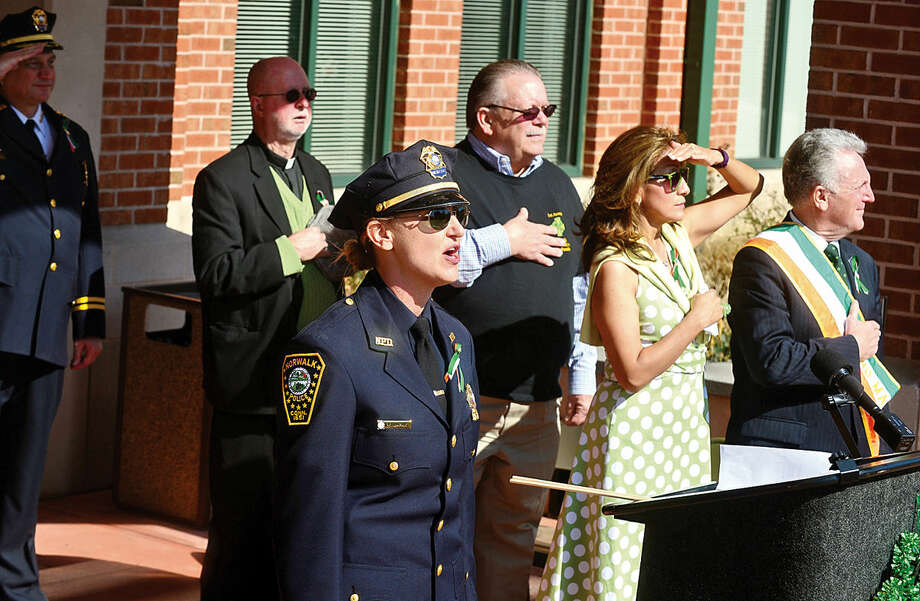 Hour photo / Erik Trautmann Norwalk police detective Kristina Lapak sings The National Anthem as the Norwalk Police Department Emerald League holds a ceremony in front of police headquarters before the first St. Patrick's Day parade Thursday.