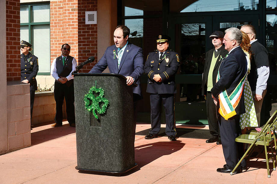 Hour photo / Erik Trautmann The Norwalk Police Department Emerald League president Brendon Collins leads a ceremony in front of police headquarters before the first St. Patrick's Day parade Thursday.