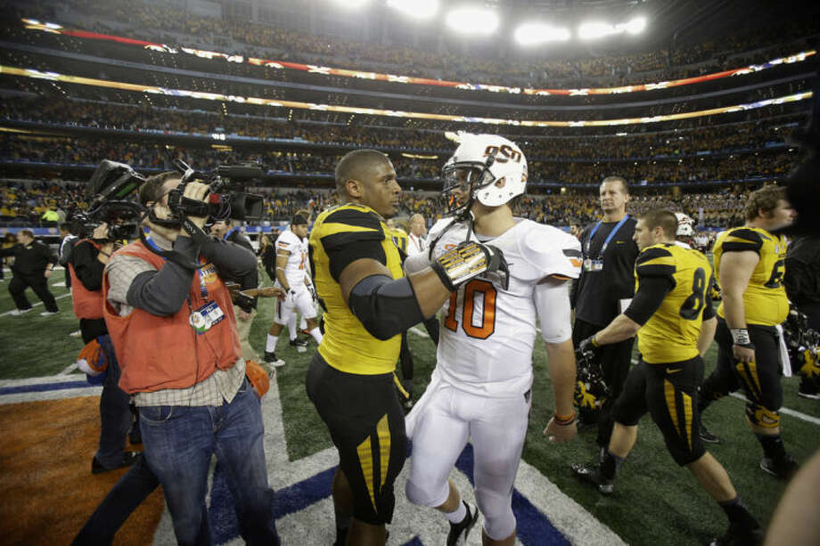 In this Jan. 3, 2014 photo, Missouri defensive lineman Michael Sam (52) and Oklahoma State quarterback Clint Chelf (10) greet each other on the field after the Cotton Bowl NCAA college football game, in Arlington, Texas. Missouri's All-America defensive end came out to the entire country Sunday, Feb. 9, 2014, and could become the first openly homosexual player in the NFL. (AP Photo/Tim Sharp)