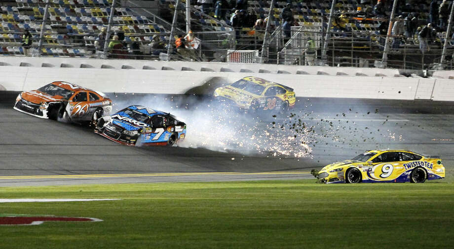 Alex Bowman (7), Jeb Burton (26), Sam Hornish Jr. (9), and David Gilliland (38) crash during the second of two qualifying races for the Daytona 500 NASCAR Sprint Cup series auto race at Daytona International Speedway in Daytona Beach, Fla., Thursday, Feb. 19, 2015. (AP Photo/Terry Renna)