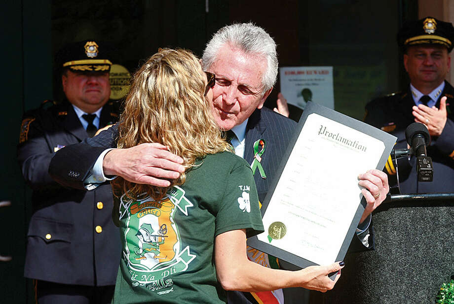 Hour photo / Erik Trautmann Norwalk mayor Harry Rilling hugs Kimberley Murphy after dedicating the first St. Patrick's Day parade to her late husband, police officer Tim Murphy, during a ceremony organized by the Norwalk Police Department Emerald League at police headquarters Thursday.