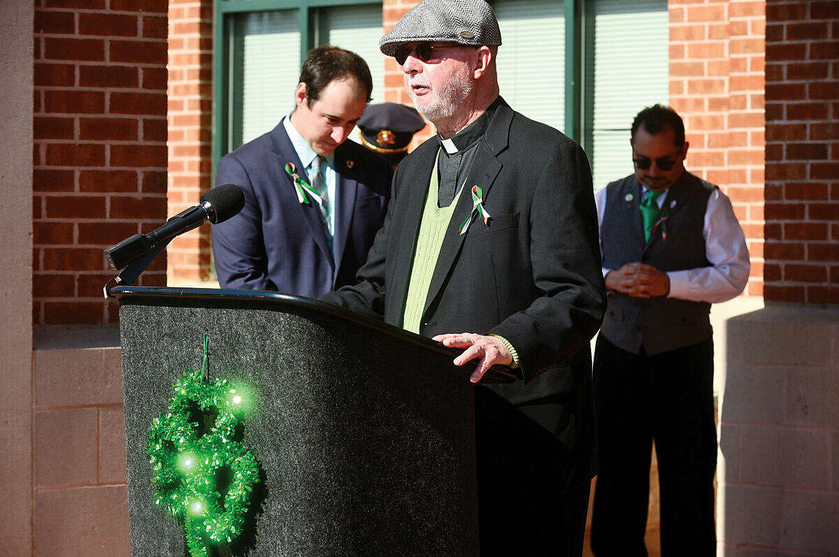 Hour photo / Erik Trautmann Father David Blanchfield gives the benediction as the Norwalk Police Department Emerald League held a ceremony in front of police headquarters before the first St. Patrick's Day parade Thursday.