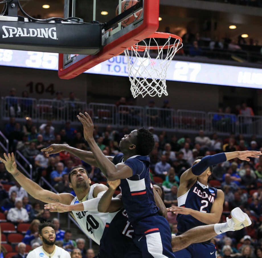 Colorado's Josh Scott (40) scores a basket against Connecticut's Kentan Facey (12), Amida Brimah, center, and Jalen Adams (2) during a first-round men's college basketball game in the NCAA Tournament in Des Moines, Iowa, Thursday, March 17, 2016. (AP Photo/Nati Harnik)