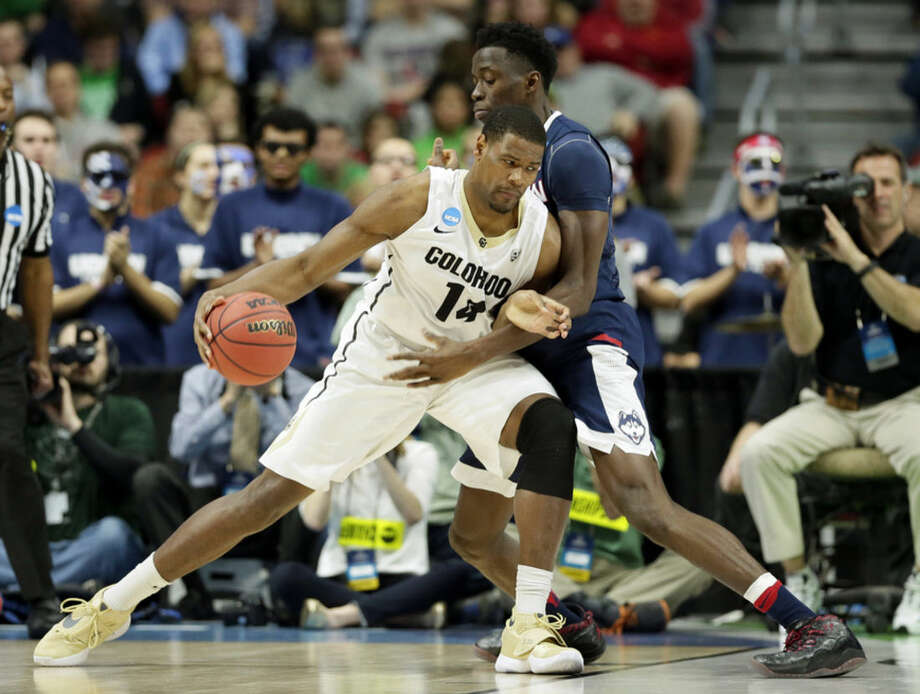 Colorado forward Tory Miller, left, looks to drive past Connecticut center Amida Brimah, right, during the first half of a first-round men's college basketball game in the NCAA Tournament, Thursday, March 17, 2016, in Des Moines, Iowa. (AP Photo/Charlie Neibergall)