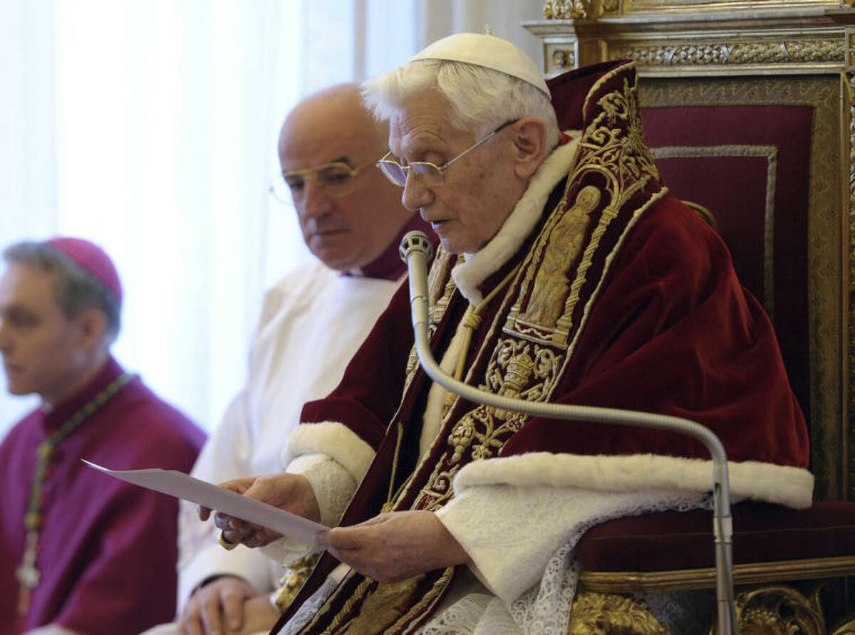 FILE - In this file photo provided by the Vatican newspaper L'Osservatore Romano on Feb. 11, 2013, Pope Benedict XVI reads a document in Latin where he announces his resignation, during a meeting of Vatican cardinals, at the Vatican. It was a holiday at the Vatican and Pope Benedict XVI was speaking in Latin at an arguably boring ceremony announcing new saints, so few people were paying much attention. But what Benedict said a year ago Tuesday changed the course of the 2,000-year-old Catholic Church and paved the way for the historic papacy of Pope Francis. In his soft voice and in a Latin that the cardinals present strained to understand, Benedict announced that he no longer had the