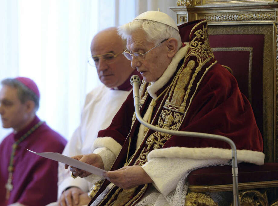 """FILE - In this file photo provided by the Vatican newspaper L'Osservatore Romano on Feb. 11, 2013, Pope Benedict XVI reads a document in Latin where he announces his resignation, during a meeting of Vatican cardinals, at the Vatican. It was a holiday at the Vatican and Pope Benedict XVI was speaking in Latin at an arguably boring ceremony announcing new saints, so few people were paying much attention. But what Benedict said a year ago Tuesday changed the course of the 2,000-year-old Catholic Church and paved the way for the historic papacy of Pope Francis. In his soft voice and in a Latin that the cardinals present strained to understand, Benedict announced that he no longer had the """"strength of mind and body"""" to be pope and would retire at the end of the month, the first pope to step down in more than half a millennium. (AP Photo/L'Osservatore Romano, ho)"""