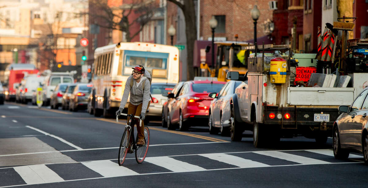 A bicyclist moves past cars stuck in traffic along Florida Avenue in the Shaw neighborhood, in Washington, Wednesday, March 16, 2016. The Metro subway system that serves the nation's capital and its Virginia and Maryland suburbs shut down for a full-day for an emergency safety inspection of its third-rail power cables. Making for unusual commute, as the lack of service is forcing some people on the roads, while others are staying home or teleworking. (AP Photo/Andrew Harnik)