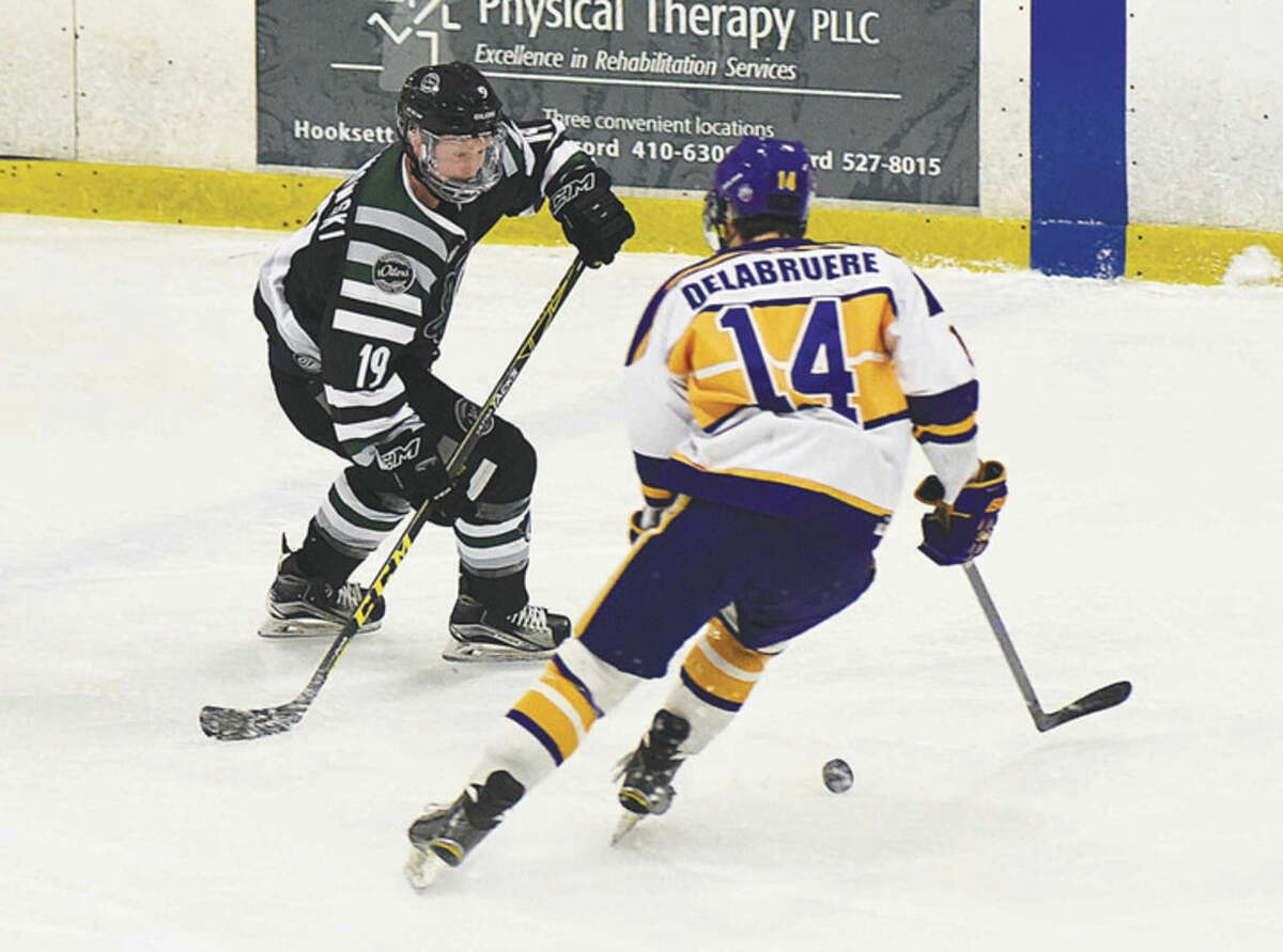 Hour photo/John Nash Connecticut Oilers skater Jason Kalinowski, left, looks to gather control of the puck as the New Hampshire Junior Monarchs Ross Delabruere moves in during the team's EHL semifinal series at the Tri-Town Arena in Hooksett, N.H. The Monarchs swept the Oilers in two games by winning 5-1 in Sunday's second game.