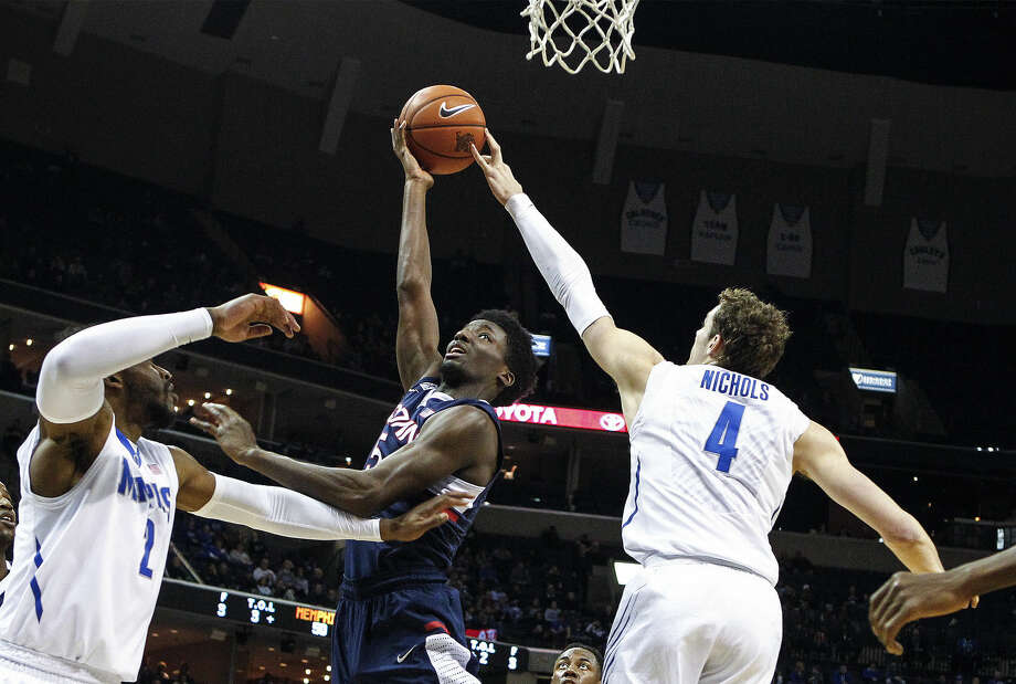 Memphis' Austin Nichols, right, blocks the shot of Connecticut's Daniel Hamilton as Memphis' Shaq Goodwin helps defend during the second half of an NCAA college basketball game Thursday, Feb. 19, 2015, in Memphis, Tenn. (AP Photo/The Commercial Appeal, Mark Weber)
