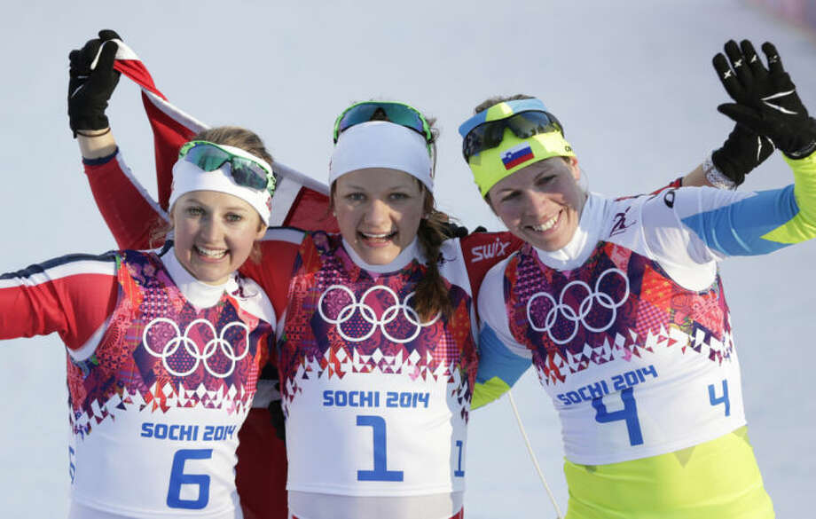 Norway's gold medal winner Maiken Caspersen Falla is flanked by silver medal winner Ingvild Flugstad Oestberg from Norway, left, and Slovenia's bronze medal winner Vesna Fabjan after the women's cross-country sprint the 2014 Winter Olympics, Tuesday, Feb. 11, 2014, in Krasnaya Polyana, Russia. (AP Photo/Matthias Schrader)