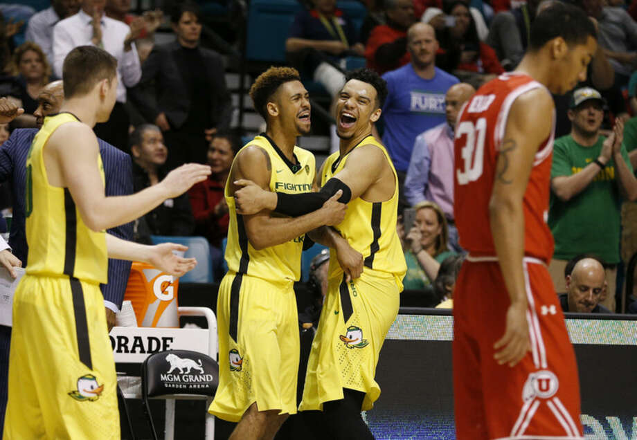 Oregon guard Tyler Dorsey, center left, embraces forward Dillon Brooks as they celebrate after Oregon defeated Utah in an NCAA college basketball game in the championship of the Pac-12 men's tournament Saturday, March 12, 2016, in Las Vegas. Oregon won 88-57. (AP Photo/John Locher)