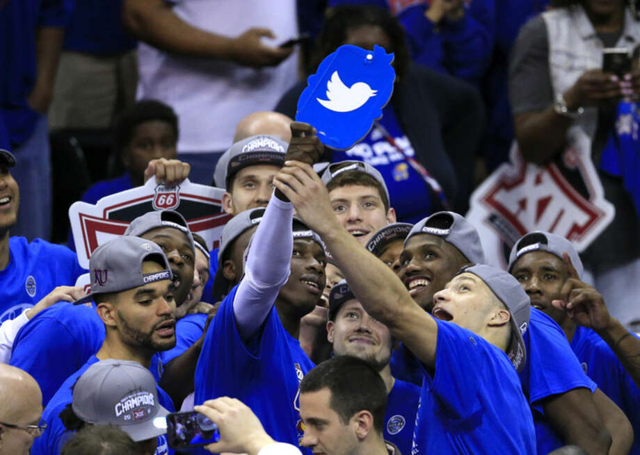 The Kansas Jayhawks pose for a team photo after winning an NCAA college basketball game against West Virginia in the finals of the Big 12 conference tournament in Kansas City, Mo., Saturday, March 12, 2016. (AP Photo/Orlin Wagner)