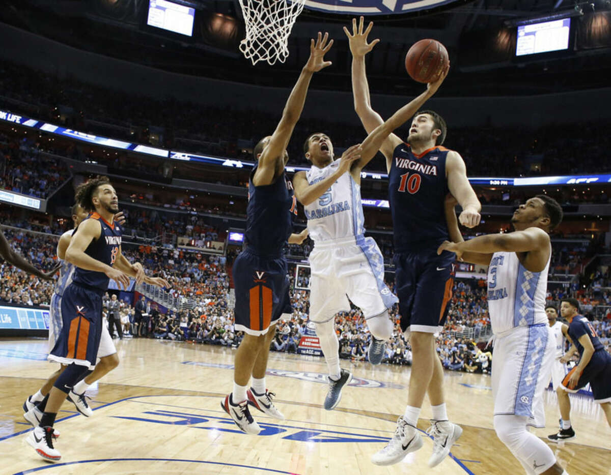 North Carolina guard Marcus Paige (5) shoots as Virginia center Mike Tobey (10) Virginia guard Malcolm Brogdon (15) defend during the first half of an NCAA college basketball game in the championship of the Atlantic Coast Conference tournament, Saturday, March 12, 2016, in Washington . North Carolina defeated Virginia 61-57. (AP Photo/Alex Brandon)