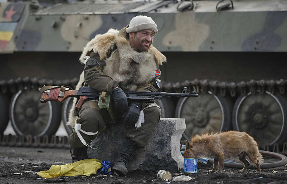 A Russia-backed rebel rests as a dog eats from a can in Debaltseve, Ukraine, Friday, Feb. 20, 2015. After weeks of relentless fighting, the embattled Ukrainian rail hub of Debaltseve fell Wednesday to Russia-backed separatists, who hoisted a flag in triumph over the town. The Ukrainian president confirmed that he had ordered troops to pull out and the rebels reported taking hundreds of soldiers captive.(AP Photo/Vadim Ghirda)