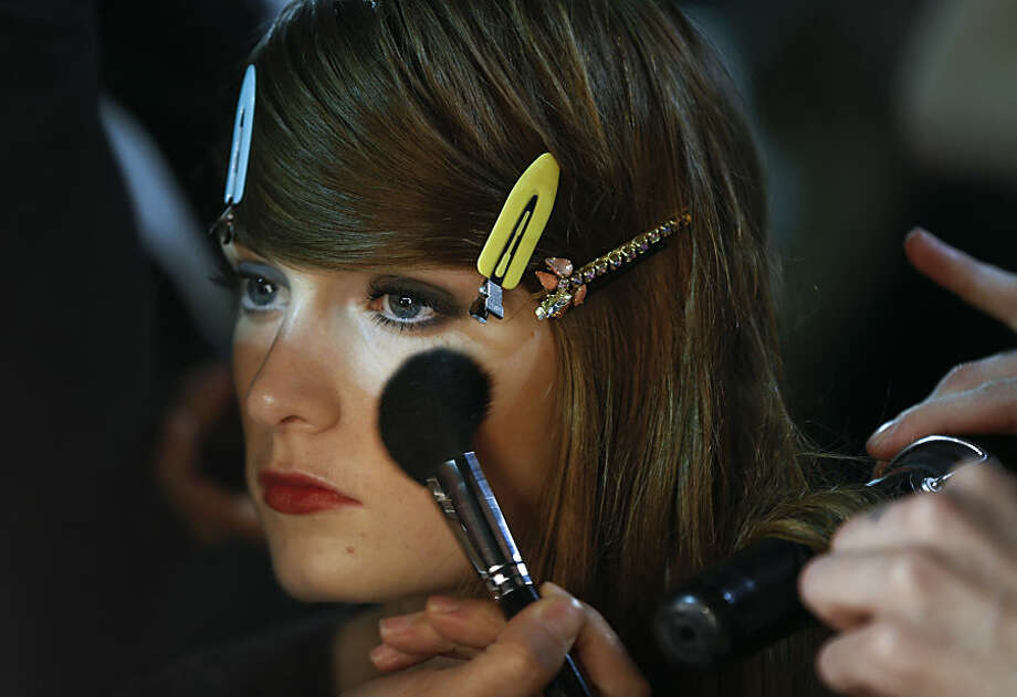 A model is prepared backstage before the designer Bora Aksu fashion show during the Autumn/Winter 2015 show at London Fashion Week in London, Friday, Feb. 20, 2015. (AP Photo/Kirsty Wigglesworth)