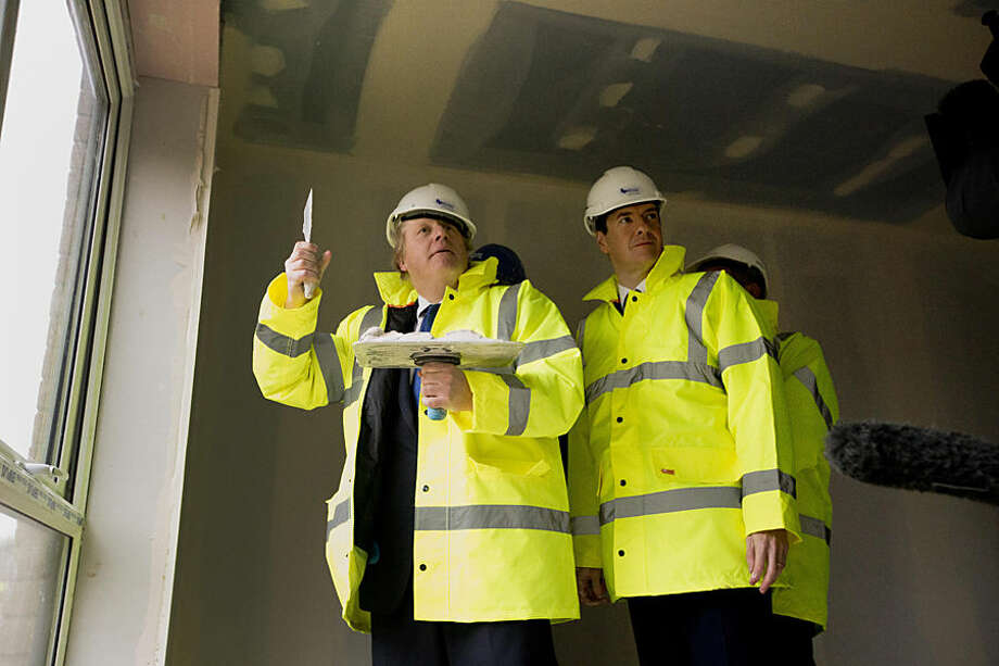 After a short demonstration on plastering, Britain's Chancellor of the Exchequer George Osborne, centre right, and London mayor Boris Johnson make an attempt to plaster, during their visit to the Aura residential development which is under construction, in the Edgware district, of north London, Friday, Feb. 20, 2015. Osborne and Johnson earlier on Friday announced plans to identify public sector sites in London for future housing developments and to increase 24-hour rail services across more underground tube lines, the London Overground trains and the London Docklands Light Railway in coming years. (AP Photo/Matt Dunham, Pool)