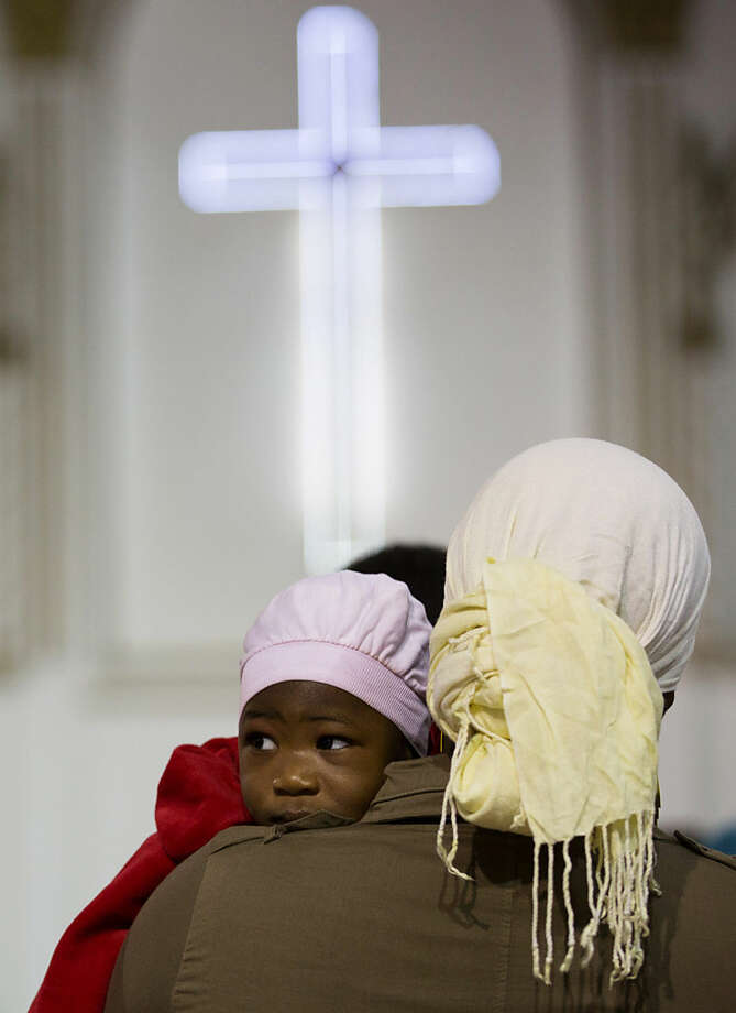 An African Christian mother and her child attend mass at Anglican church in Tripoli, Libya, Friday, Feb. 20, 2015. Numbers here have dropped since fighting in the capital last summer forced many expatriate workers to leave Libya. (AP Photo/Mohamed Ben Khalifa)