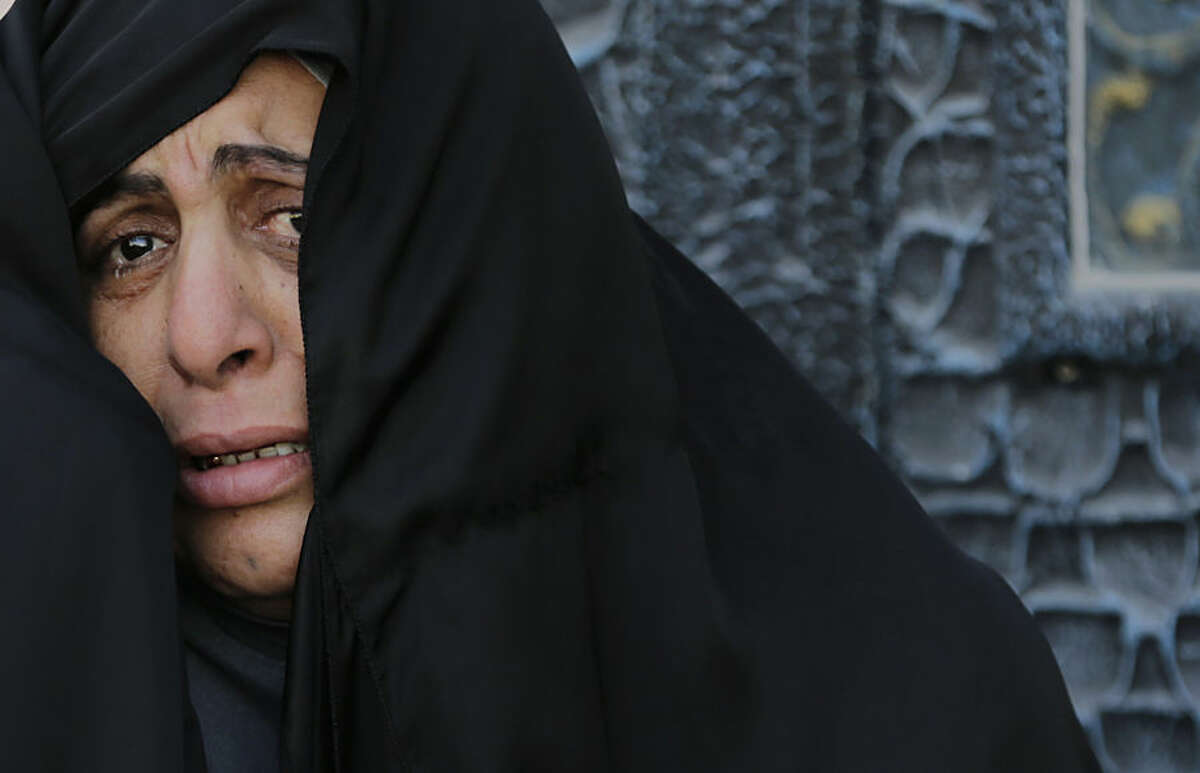 A Bahraini mourner cries as she watches the funeral of Sayed Mohamed Sayed Kadhim, in Saar, Bahrain, Friday, Feb. 20, 2015. Mourners chanted anti-government slogans during a politically charged funeral procession. Relatives and opposition groups said Sayed Mohammed died from heavy teargas during earlier clashes in the village. Clashes erupted when angry protesters clashed with police surrounding the village after the funeral. (AP Photo / Hasan Jamali)