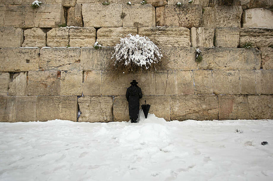 An ultra-Orthodox Jewish man prays at the Western Wall, the holiest site where Jews can pray in Jerusalem's old city, Friday, Feb. 20, 2015. A heavy winter storm descended on parts of the Middle East on Friday, with snow forcing the closure of all roads leading in and out of Jerusalem and sprinkling Israel's desert with a rare layer of white. (AP Photo/Sebastian Scheiner)
