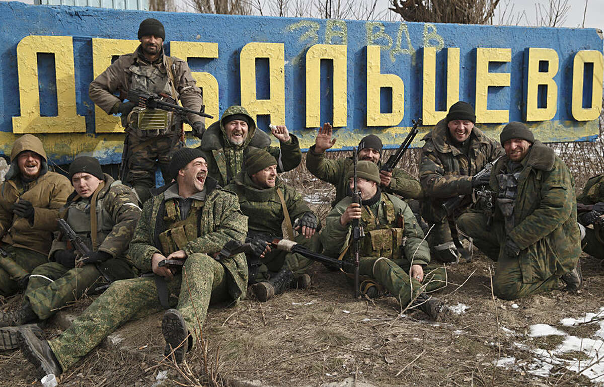 Russia-backed rebels pose by a road sign at the entrance in Debaltseve, Ukraine, Friday, Feb. 20, 2015, after checking the access road into town for mines left behind by retreating Ukrainian government troops. After weeks of relentless fighting, the embattled Ukrainian rail hub of Debaltseve fell Wednesday to Russia-backed separatists, who hoisted a flag in triumph over the town. The Ukrainian president confirmed that he had ordered troops to pull out and the rebels reported taking hundreds of soldiers captive. (AP Photo/Vadim Ghirda)