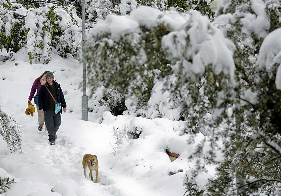 A couple walk their dog in Jerusalem, Friday, Feb. 20, 2015. A heavy winter storm descended on parts of the Middle East on Friday, with snow forcing the closure of all roads leading in and out of Jerusalem and sprinkling Israel's desert with a rare layer of white. (AP Photo/Dusan Vranic)