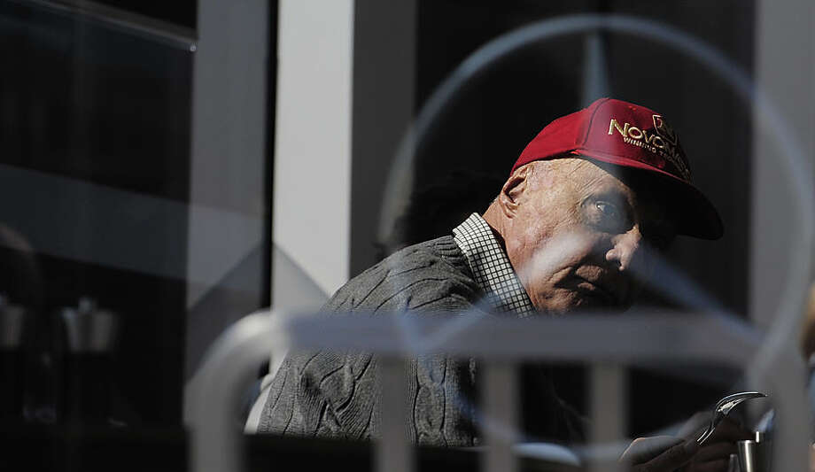 Former Austrian Formula One driver Niki Lauda is pictured through a glass window, during the 2015 Formula One testing, at the Barcelona Catalunya racetrack in Montmelo, Spain, Friday, Feb. 20, 2015. (AP Photo/Manu Fernandez)