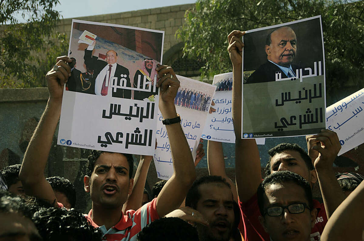Protesters hold posters with pictures of former President Abed Rabbo Mansour Hadi during an anti-Houthi demonstration in Sanaa, Yemen, Saturday, Feb. 21, 2015. Hadi left the capital after Shiite rebels who surrounded his house let him go under international and local pressure, aides close to him said Saturday. Hadi had been under house arrest for several weeks following a coup by Shiite Houthi rebels. Posters in Arabic read,