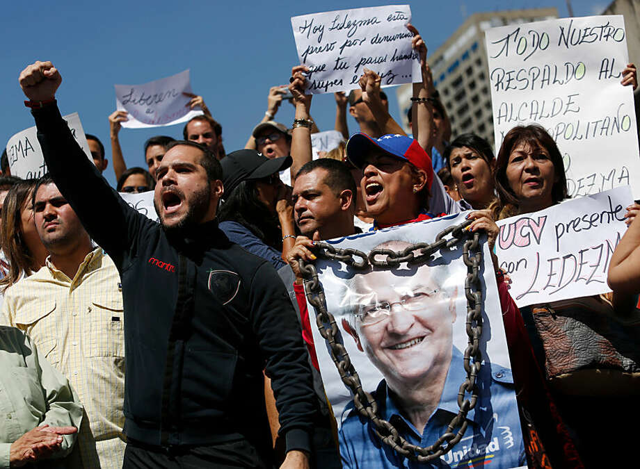 A supporter of Caracas Mayor Antonio Ledezma holds a poster of him with chains during a protest demanding his release in Caracas, Venezuela, Friday, Feb. 20, 2015. Demonstrators are condemning last night's surprise arrest of Ledezma for allegedly plotting to overthrow the government of President Nicolas Maduro. Late Thursday Maduro said Ledezma, one of the most vocal opposition leaders, would be punished for trying to sow unrest in Venezuela. (AP Photo/Alejandro Cegarra)
