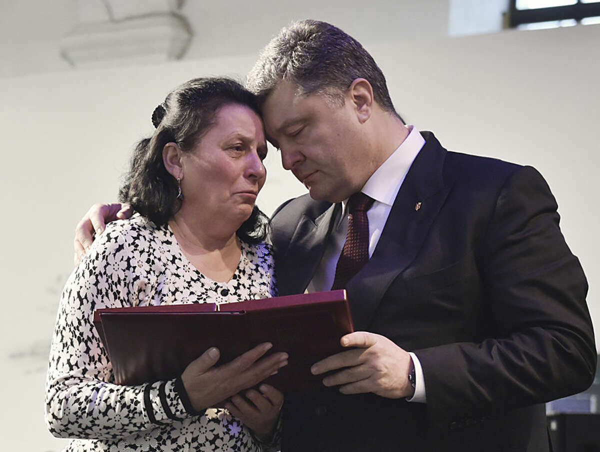 Ukrainian President Petro Poroshenko, right, presents a Hero of Ukraine award to a relative of an activist killed a year ago during mass protests, at the award ceremony in Kiev, Ukraine, Friday, Feb. 20, 2015. (AP Photo/Mykola Lazarenko, Pool)