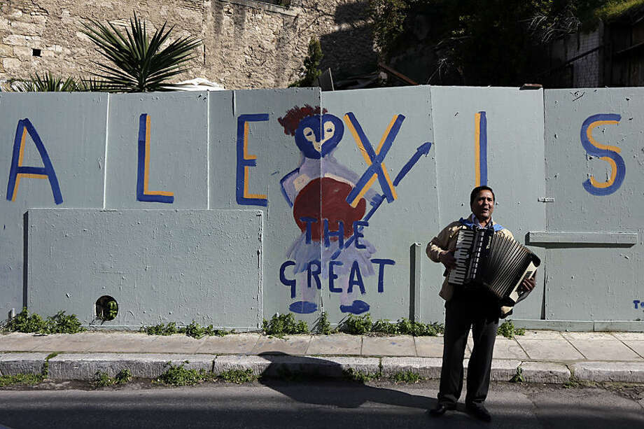A busker plays music in front of a graffiti that refer to Greece's Prime Minister Alexis Tsipras in the traditional Plaka district of Athens on Saturday, Feb. 21, 2015. Greece's government starts working on drafting a series of economic reforms it must present to the other euro zone finance ministers on Monday, as part of an agreement reached Friday to extend the country's European loan agreement. (AP Photo/Thanassis Stavrakis)