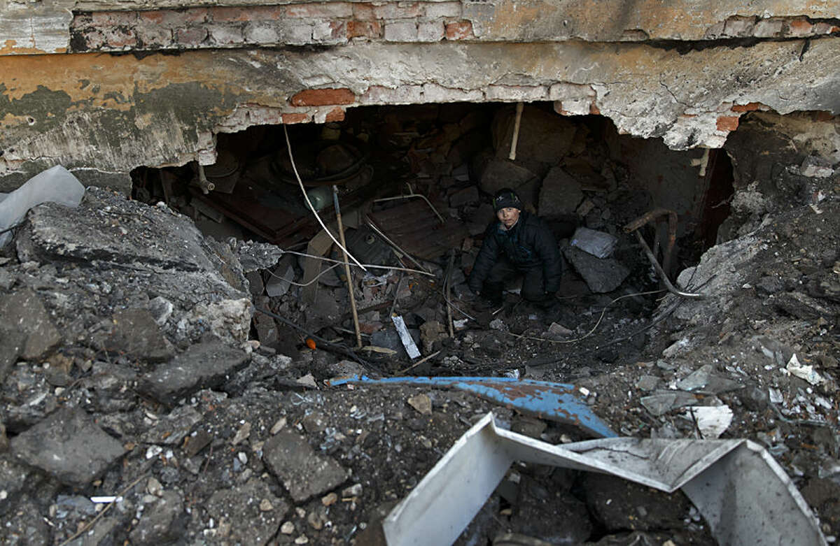 Maxim, 8 years-old, walks inside the damaged apartment building where his family live, in Debaltseve, Ukraine, Friday, Feb. 20, 2015. After weeks of relentless fighting, the embattled Ukrainian rail hub of Debaltseve fell Wednesday to Russia-backed separatists, who hoisted a flag in triumph over the town. The Ukrainian president confirmed that he had ordered troops to pull out and the rebels reported taking hundreds of soldiers captive.(AP Photo/Vadim Ghirda)